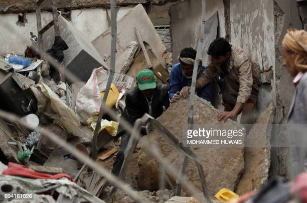 Yemenis check the destruction following a suspected Saudiled coalition air strike in Sanaa on June 9 2017 Four civilians including two teenagers died...