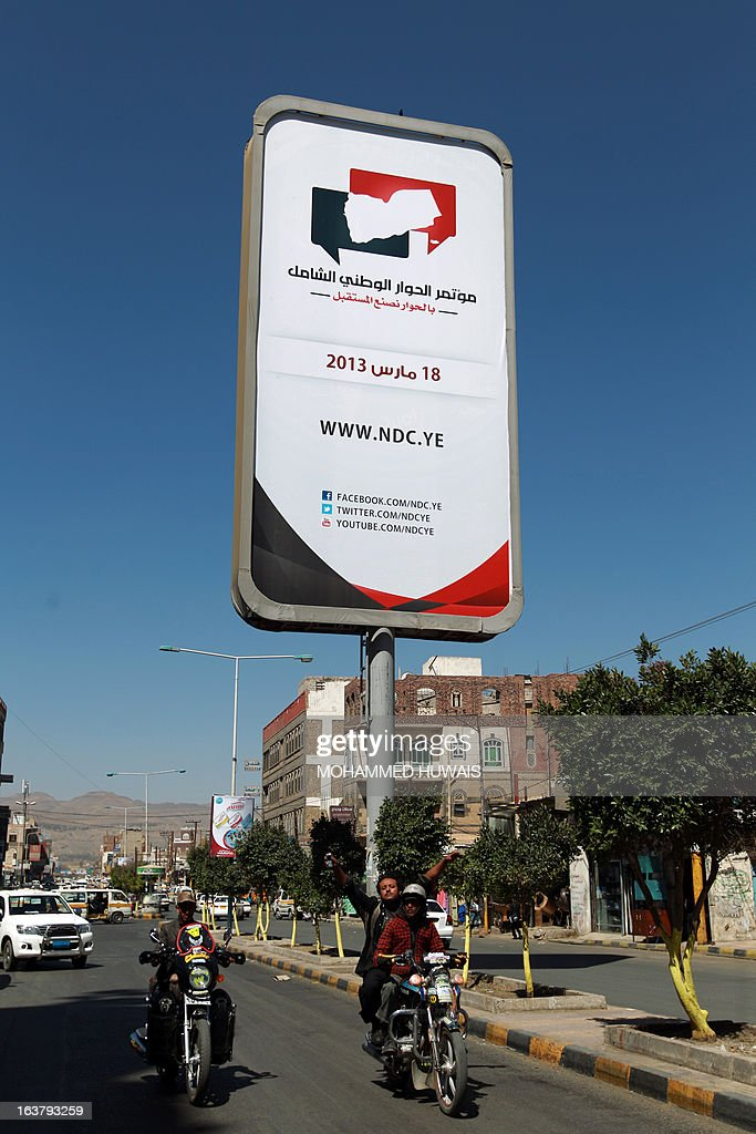 Yemenis drive under a billboard advertising Yemen's national dialogue conference in Sanaa on March 16, 2013. Yemen, the only country where an Arab Spring revolt led to a negotiated settlement, is to launch a UN-backed national dialogue on March 18, aimed at drawing the state's divisive players towards a reconciliation. AFP PHOTO/ MOHAMMED HUWAIS