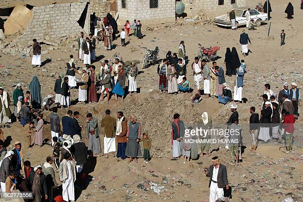 Yemenis gather around a crater reportedly caused by a Saudiled airstrike targeting the outskirts of the capital Sanaa on December 29 2015 Since March...