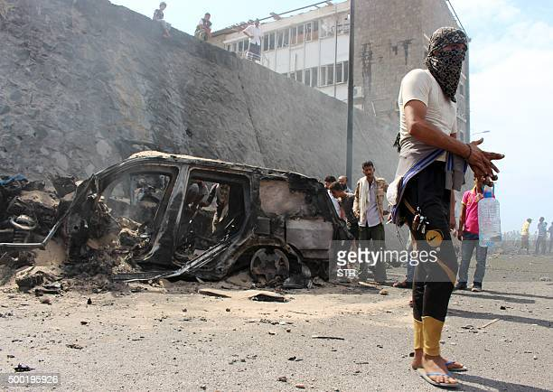 Yemenis gather around the wreckage of a car at the site of a blast that hit the convoy of the governor of Aden Jaafar Saad in the Tawahi...