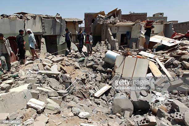 Yemenis gather near the rubble of houses near Sanaa Airport on March 31 2015 which were destroyed by an air strike as Saudiled coalition warplanes...