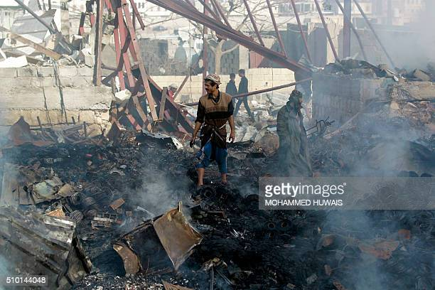 Yemenis inspect the damage at a sewing workshop that was hit by a Saudiled coalition air strike in the capital Sanaa on February 14 2016 The factory...