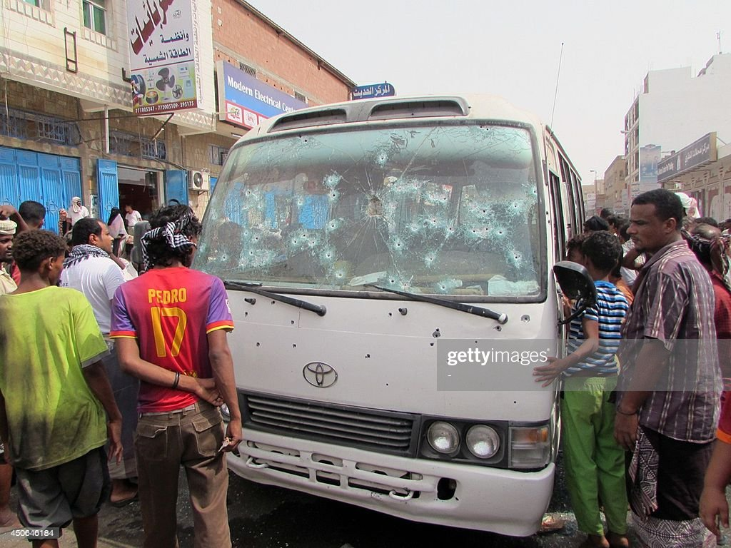 Yemenis look at an army minibus that was attacked by a gunman with an assault rifle as it was carrying members of staff from a military hospital on June 15, 2014 in Yemen's main southern city of Aden. The attack killed eight passengers, among them two women, and wounded 12 others.