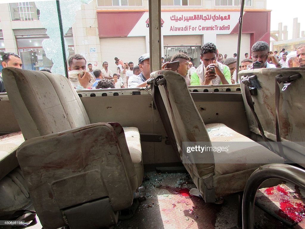 Yemenis look at the inside of an army minibus that was attacked by a gunman with an assault rifle as it was carrying members of staff from a military hospital on June 15, 2014 in Yemen's main southern city of Aden. The attack killed eight passengers, among them two women, and wounded 12 others. AFP PHOTO / STR
