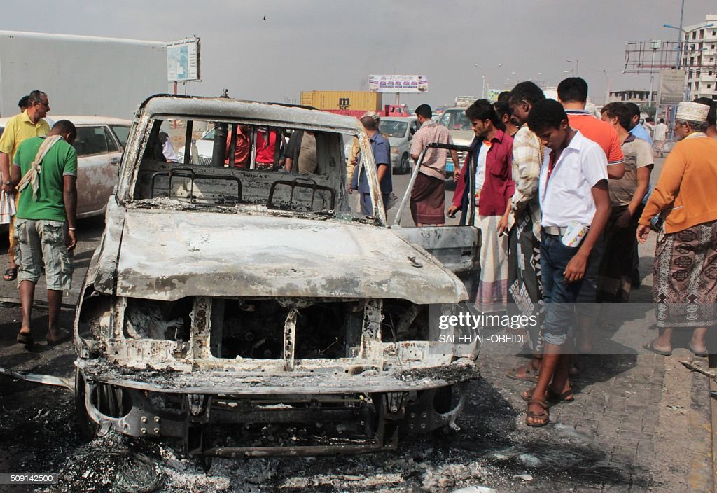 Yemenis look at the wreckage of a vehicle on February 9, 2016, in the aftermath of clashes between forces loyal to Saudi-backed President Abedrabbo Mansour Hadi and al-Qaeda members in the Mansura suburb of Aden. Yemeni forces clashed with Al-Qaeda militants in Aden as the Saudi-led coalition provided air cover, in a bid to drive the jihadists out of the city, security officials said. / AFP / SALEH AL-OBEIDI