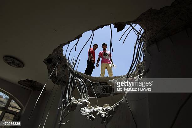 Yemenis look down through a hole in the roof of a house which was damaged the day before during an air strike by Saudiled coalition warplanes on the...