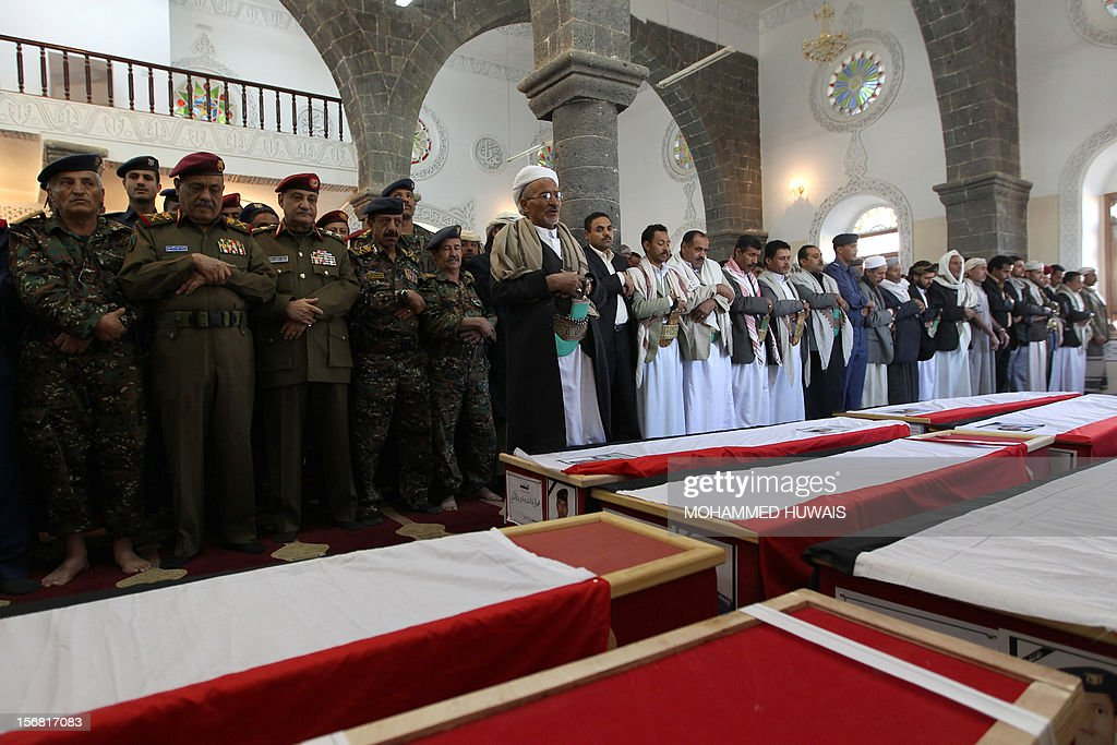 Yemenis pray over the coffins of ten people who were killed in a crash of a military plane the previous day, during a funeral service in Sanaa on November 22, 2012. The plane crashed on November 20 as it tried to make an emergency landing when an engine failed, accorading Yemen's defence ministry. AFP PHOTO/MOHAMMED HUWAIS