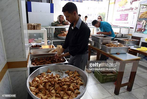 Yemenis queue to buy fried 'sambusa' or samosa during the Muslim holy fasting month of Ramadan in the capital Sanaa on June 28 2015 AFP PHOTO /...