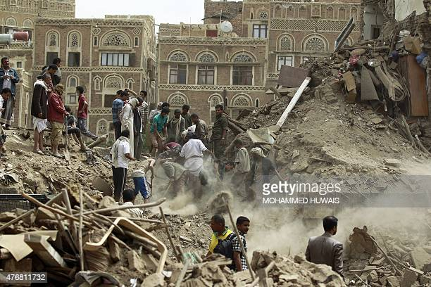 Yemenis search for survivors under the rubble of houses in the UNESCOlisted heritage site in the old city of Yemeni capital Sanaa on June 12 2015...