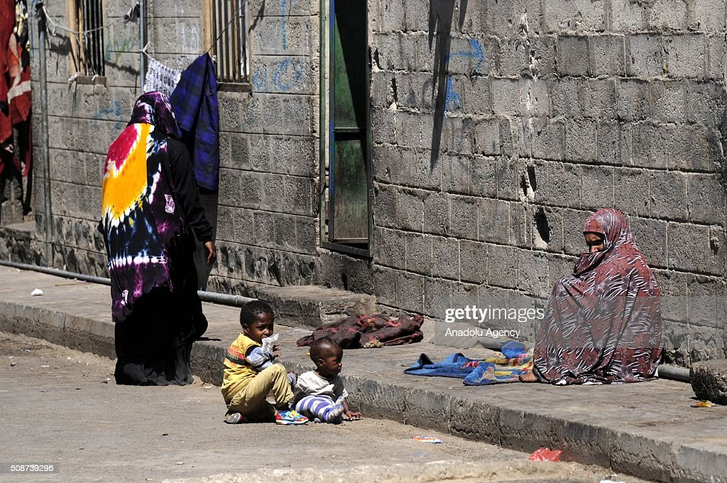Yemenis sit on the pavement outside their houses in Savan neighborhood as Saudi-led airstrikes continue in Sana'a, Yemen on February 6, 2016.