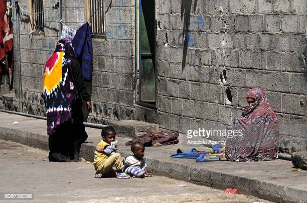Yemenis sit on the pavement outside their houses in Savan neighborhood as Saudiled airstrikes continue in Sana'a Yemen on February 6 2016