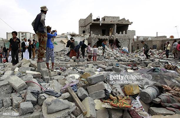 Yemenis stand amid the ruins of buildings destroyed in an airstrike by the Saudiled coalition on the capital Sanaa on July 13 2015 Air strikes in...