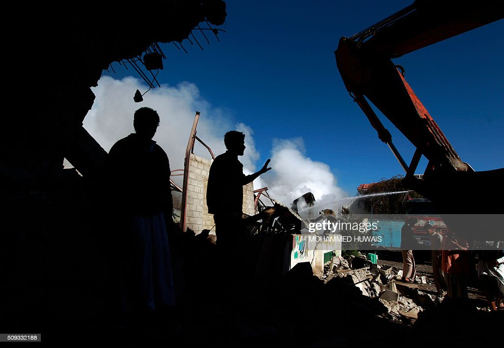 Yemenis stand amid the ruins of buildings destroyed in an air-strike by the Saudi-led coalition on February 10, 2016 in the capital Sanaa. The coalition has been carrying out air strikes against Iran-backed rebels across Yemen since March. / AFP / MOHAMMED HUWAIS