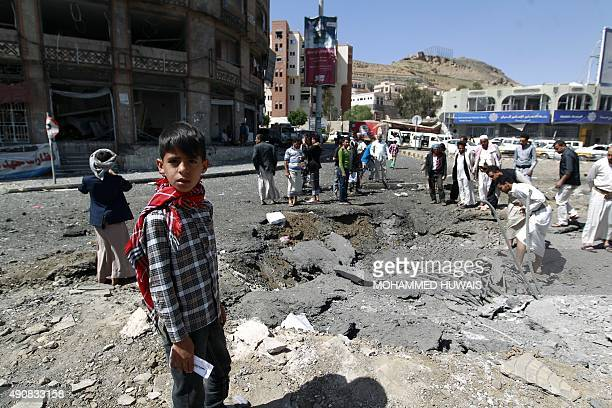 Yemenis stand around a crater reportedly caused by air strikes carried out by the Saudiled coalition in the capital Sanaa on October 1 2015 A...