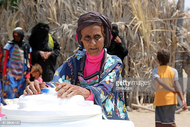 Yemenis stand near water containers and their food supplies provided by a local charity in an impoverished coastal village on the outskirts of the...