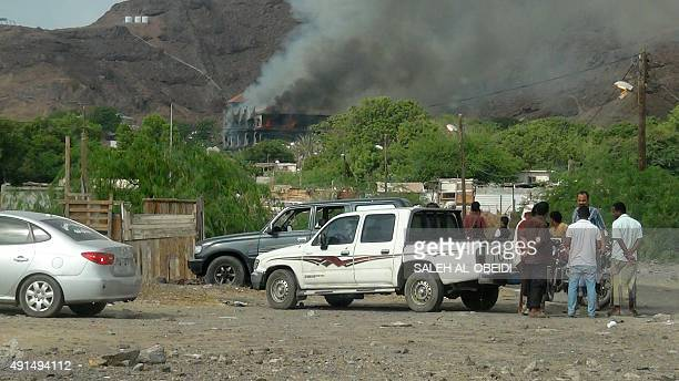 Yemenis stand next to vehicles as flames and smoke rise from Sheikh bin Farid palace used as a base by the Saudiled coalition forces after it was hit...