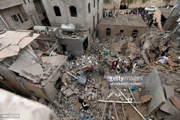 Yemenis stand on the rubble of houses destroyed in a suspected Saudiled coalition air strike in Sanaa on June 9 2017 Four civilians including two...