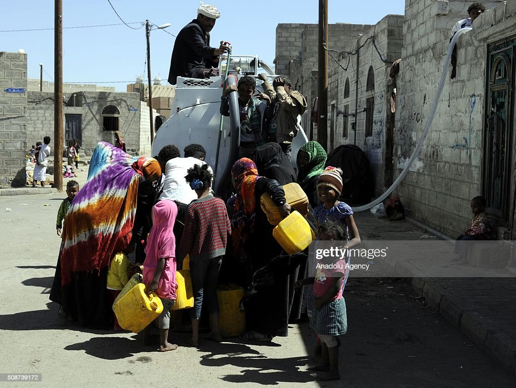 Yemenis try to fill their plastic cans with water in Savan neighborhood as Saudi-led airstrikes continue in Sana'a, Yemen on February 6, 2016.