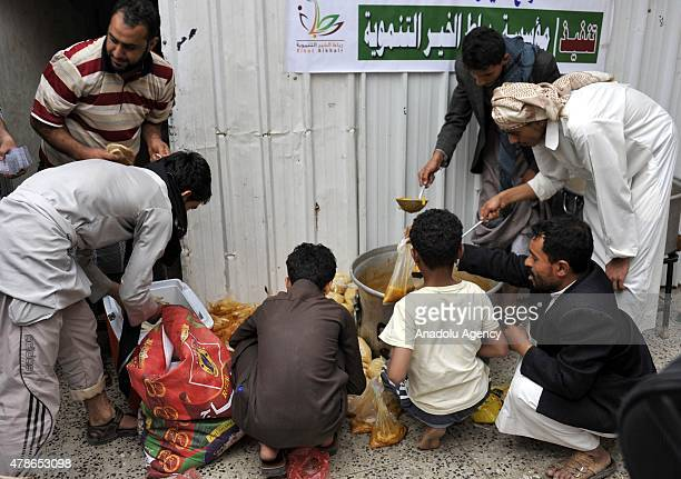 Yemenis wait in line at a school garden in Sumeyla district of capital Sanaa to receive food aids provided by the union of nongovernmental...