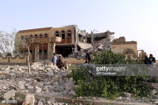 Yemenis walk past a building housing branches of the Finance Ministry and Central Bank that was heavily damaged in an airstrike by the Saudiled...