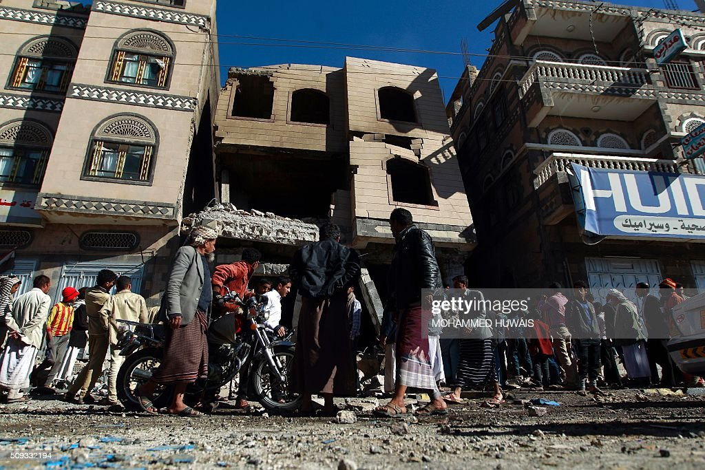 Yemenis walk past the ruins of buildings destroyed in an air-strike by the Saudi-led coalition on February 10, 2016 in the capital Sanaa. The coalition has been carrying out air strikes against Iran-backed rebels across Yemen since March. / AFP / MOHAMMED HUWAIS