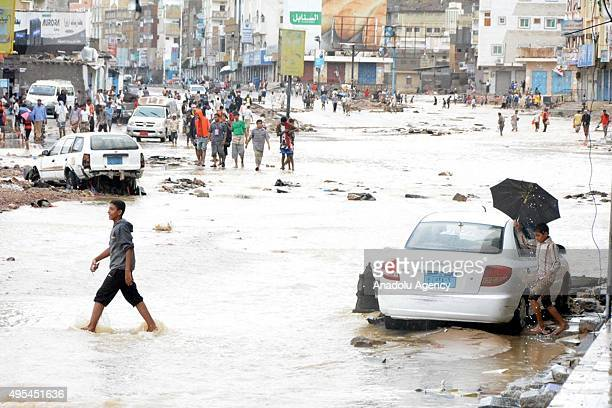 Yemenis walk past the vehicles damaged by wind and heavy raincaused floodwaters as a result of Cyclone Chapala generated in the Arabian Sea on the...