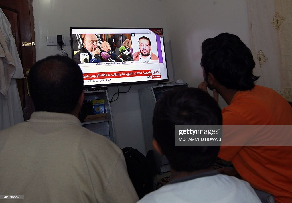 Yemenis watch a news chanel as President Abdrabuh Mansur Hadi is displayed on the screen (L) on January 22, 2015 in the capital Sanaa. Hadi, 69, who offered to quit after his palace compound was seized and residence attacked by Huthi Shiite militiamen, has ruled over Yemen for three turbulent years. AFP PHOTO / MOHAMMED HUWAIS