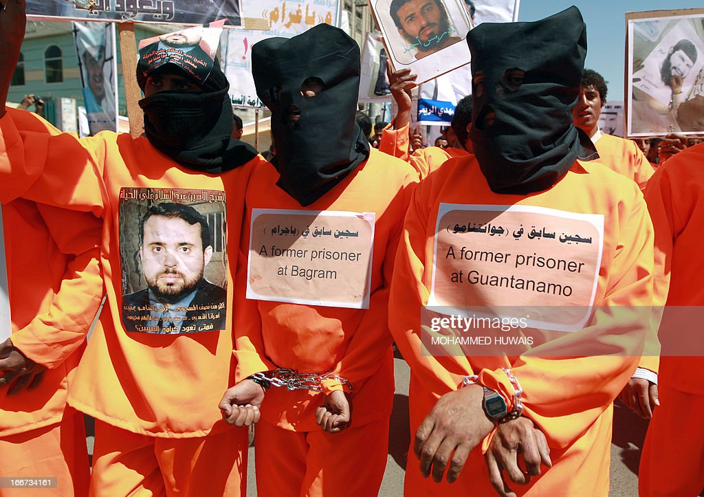Yemenis wearing orange jumpsuits, similar to those worn by prisoners at the US detention centre in Guantanamo Bay, hold a protest demanding the release of inmates on hunger strike, on April 16, 2013 outside the US embassy in Sanaa. Attorneys representing inmates at the prison have said most of the estimated 130 detainees at Guantanamo's Camp Six wing, which houses 'low-value' prisoners, were on hunger strike. AFP PHOTO/MOHAMMED HUWAIS