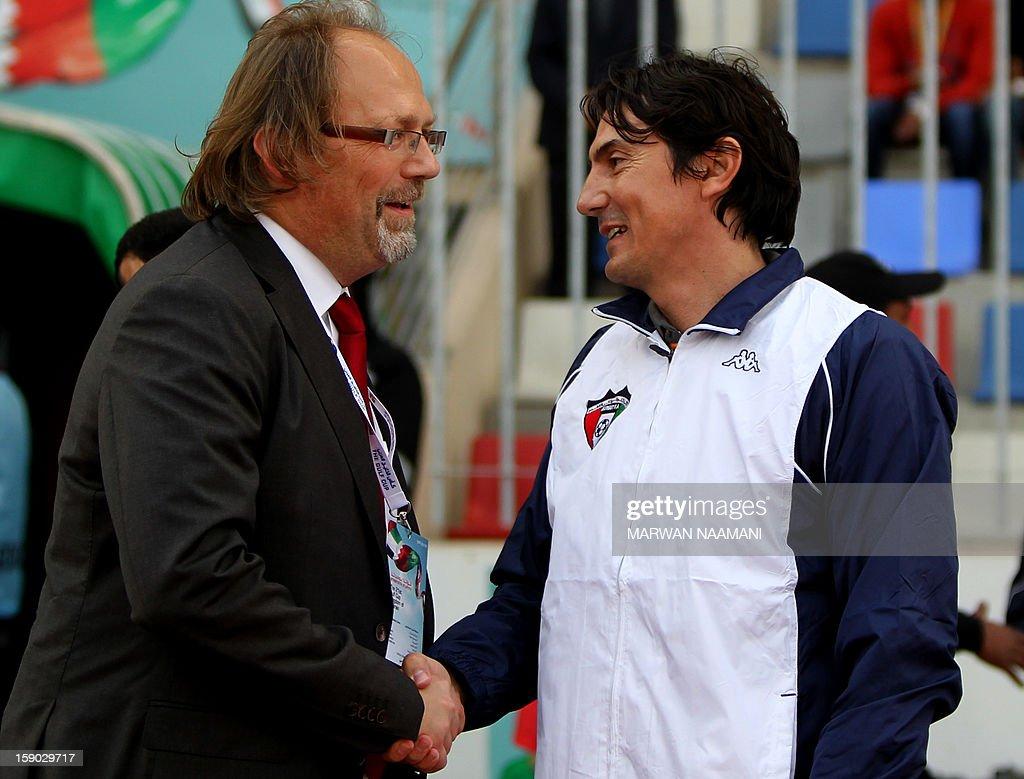 Yemen's national team's coach, Belgian Tom Saintfiet (L) shakes hands with his Kuwait's counterpart Goran Tufegdzic prior the start of the Gulf Cup football match Kuwait versus Yemen, on January 6, 2013 in Manama.