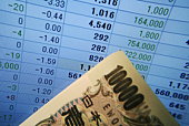 10, 100 Yen bill in front of computer screen displaying financial spreadsheet