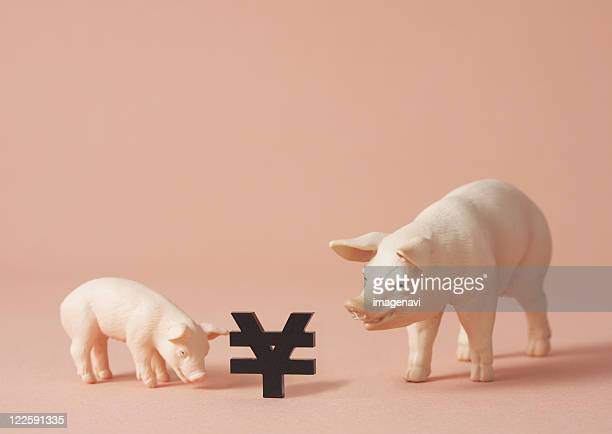 Yen sign and pig figurines