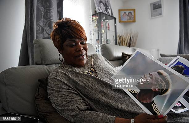 Yeo Moriba the mother of footballer Paul Pogba holds his photograph on March 16 2016 in Bussy Saint Georges east of Paris Yeo Moriba acts as her...