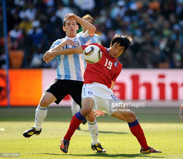 Yeom KiHun of South Korea is challenged by Maxi Rodriquez of Argentina during the 2010 FIFA World Cup South Africa Group B match between Argentina...
