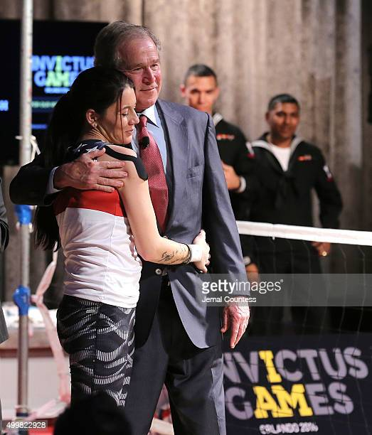 Yeoman 3rd Class Kristen Esget hugs Former President George W Bush during an event to announce a major initiative prior to the 2016 Invictus Games in...