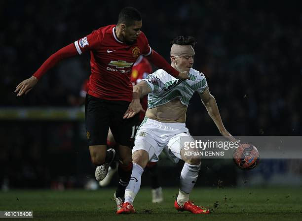 Yeovil Town's English striker Kieffer Moore holds off Manchester United's English defender Chris Smalling during the English FA Cup third round...