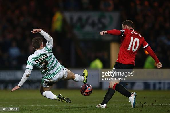 Yeovil Town's Irish midfielder Kevin Dawson dives to block a pass from Manchester United's English striker Wayne Rooney during the English FA Cup...