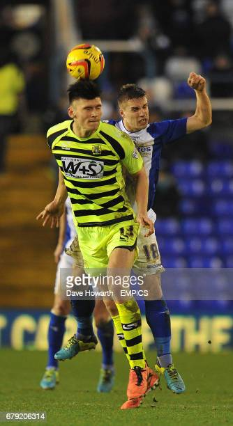 Yeovil Town's Kieffer Moore and Birmingham City's Mitch Hancox jump for the ball