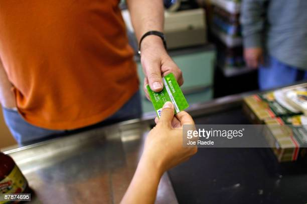 Yera Dominguez receives a credit card from a customer for payment at Lorenzo's Italian Market on May 20 2009 in Miami Florida Members of Congress...