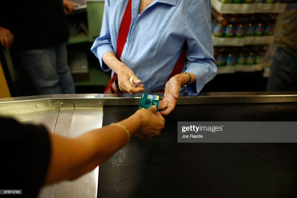 Yera Dominguez receives a credit card from a customer for payment at Lorenzo's Italian Market on May 20, 2009 in Miami, Florida. Members of Congress today passed a bill placing new restrictions on companies that issues credit. The vote follows the Senate passage of the bill, which now heads for President Obama's promised signature. The bill will curb sudden interest rate increases and hidden fees, requiring card companies to tell customers of rate increases 45 days in advance. It will also make it harder for people aged below 21 to be issued credit cards.