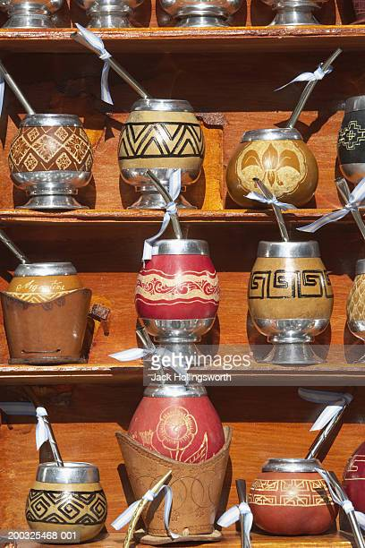 Yerba mate gourds and bombillas on shelf