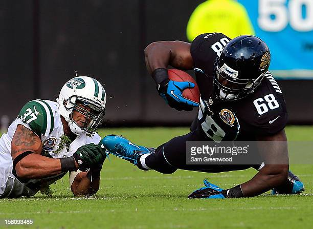 Yeremiah Bell of the New York Jets tackles Guy Whimper of the Jacksonville Jaguars during the game at EverBank Field on December 9 2012 in...