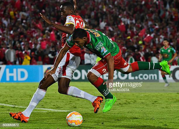 Yerri Mina of Colombia's Santa Fe vies for the ball with Ramon Abila of Argentina's Huracan during their Sudamericana Cup final football match at El...