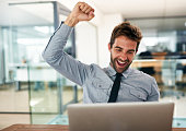 Shot of a young businessman cheering while using a laptop at his desk in an office
