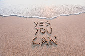 yes you can, motivational inspirational message concept written on the sand of beach