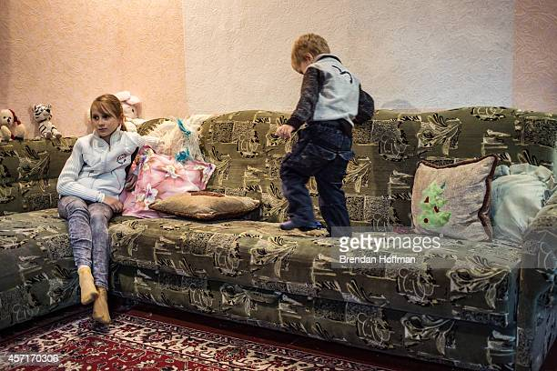 Yeva sits on the couch in the home where she her mother and her grandmother are living with a family in their church's congregation after fleeing...