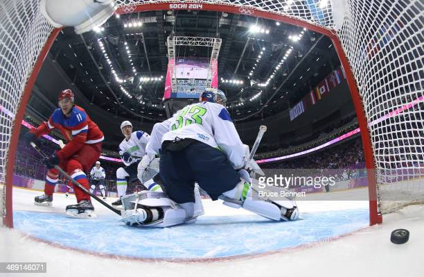 Yevgeni Malkin of Russia scores on Robert Kristan of Slovenia in the first period during the Men's Ice Hockey Preliminary Round Group A game on day...