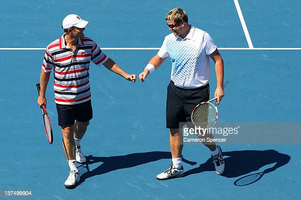 Yevgeny Kafelnikov of Russia and Wayne Ferreira of Russia talk tactics in their Legends double's match against Guy Forget and Henri Leconte of France...