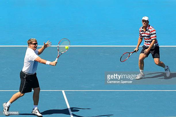 Yevgeny Kafelnikov of Russia plays a backhand with Wayne Ferreira of Russia in their Legends double's match against Guy Forget and Henri Leconte of...