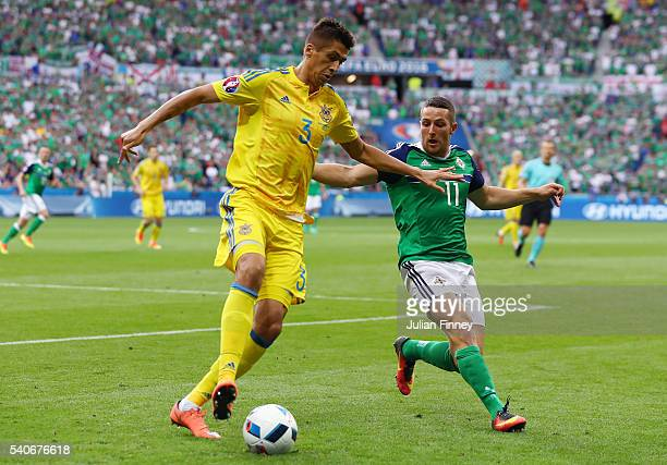 Yevhen Khacheridi of Ukraine and Conor Washington of Northern Ireland compete for the ball during the UEFA EURO 2016 Group C match between Ukraine...