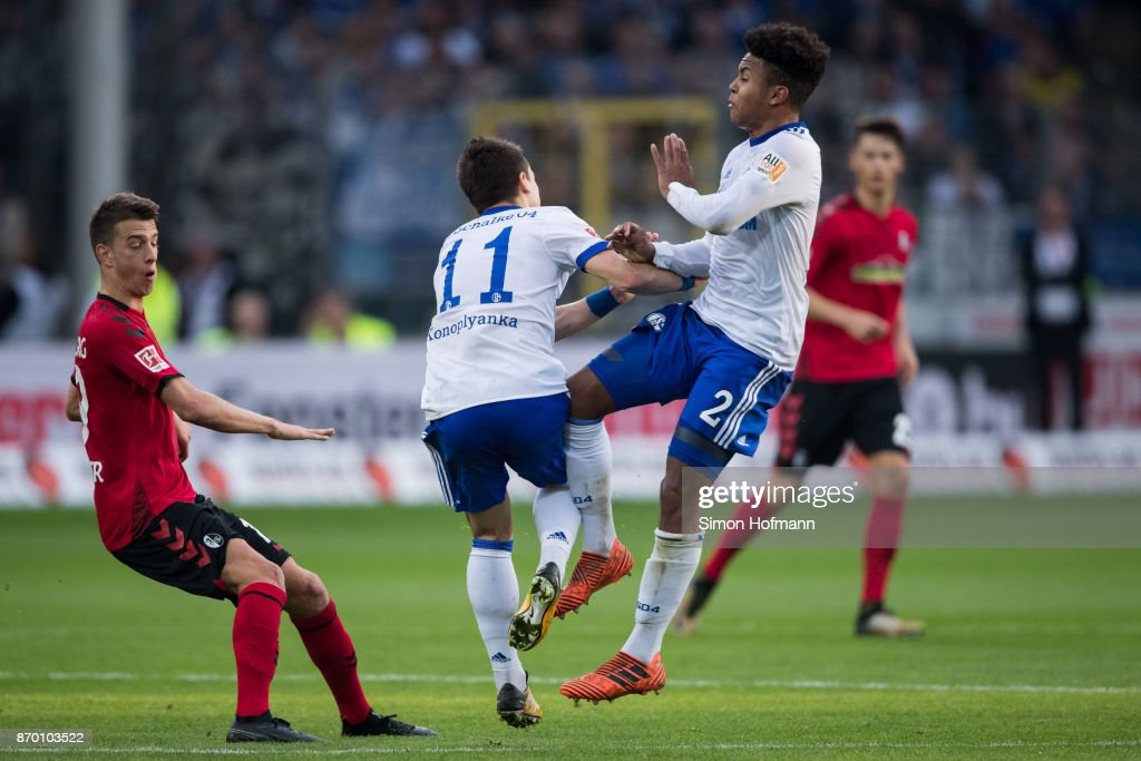 Yevhen Konoplyanka of Schalke (C) gets injured a he gets hit by team mate Weston McKennie (R) during the Bundesliga match between Sport-Club Freiburg and FC Schalke 04 at Schwarzwald-Stadion on November 4, 2017 in Freiburg im Breisgau, Germany.
